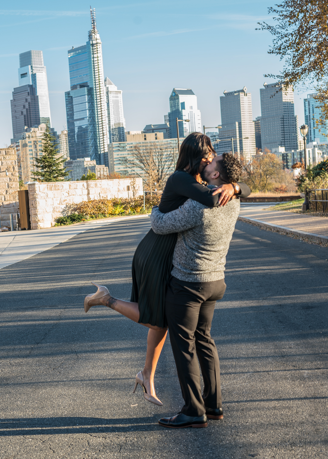 Black couple hugging and kissing in front of Philadelphia cityscape.