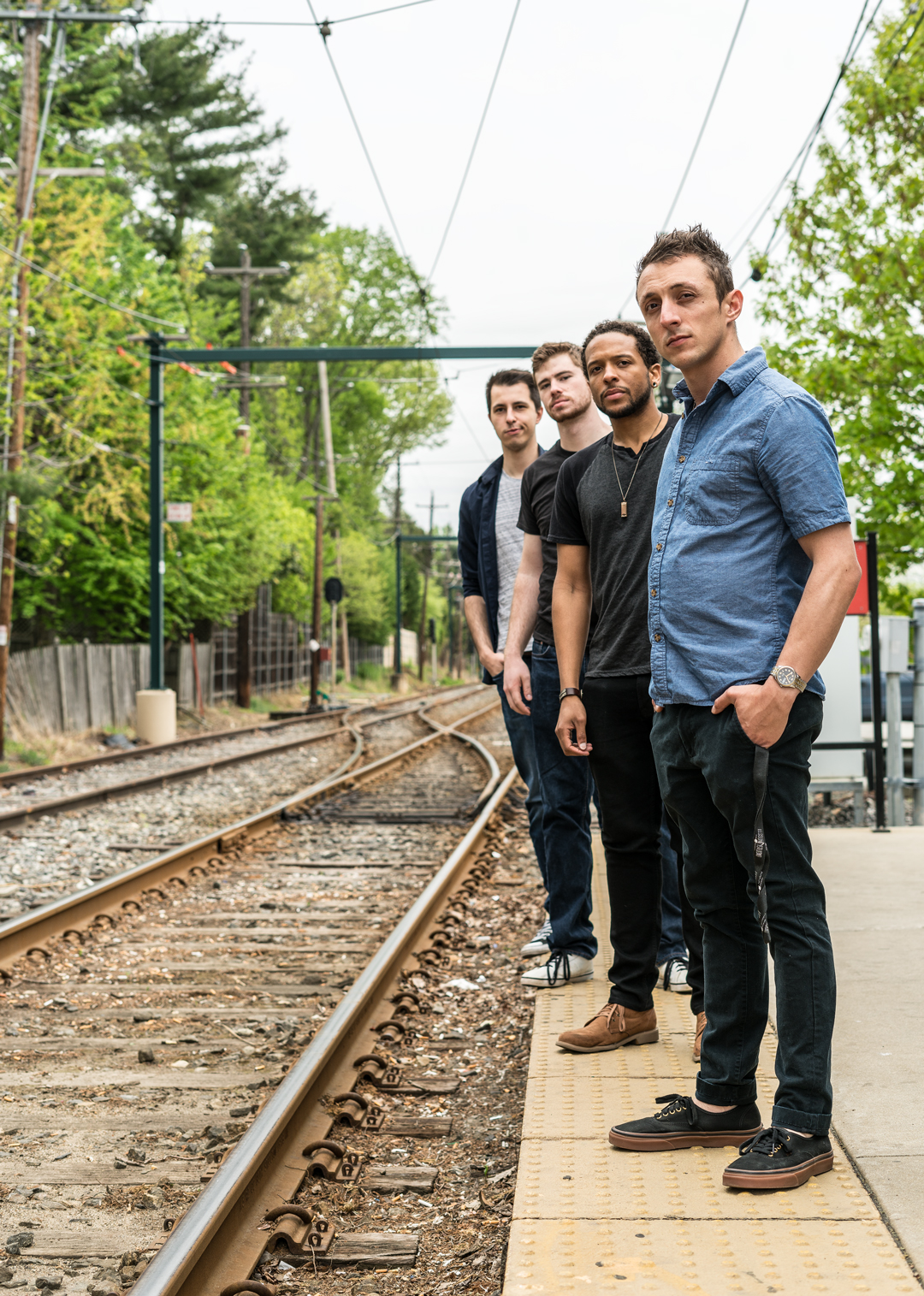 Multicultural bandmembers standing in line next to train tracks at a train station.