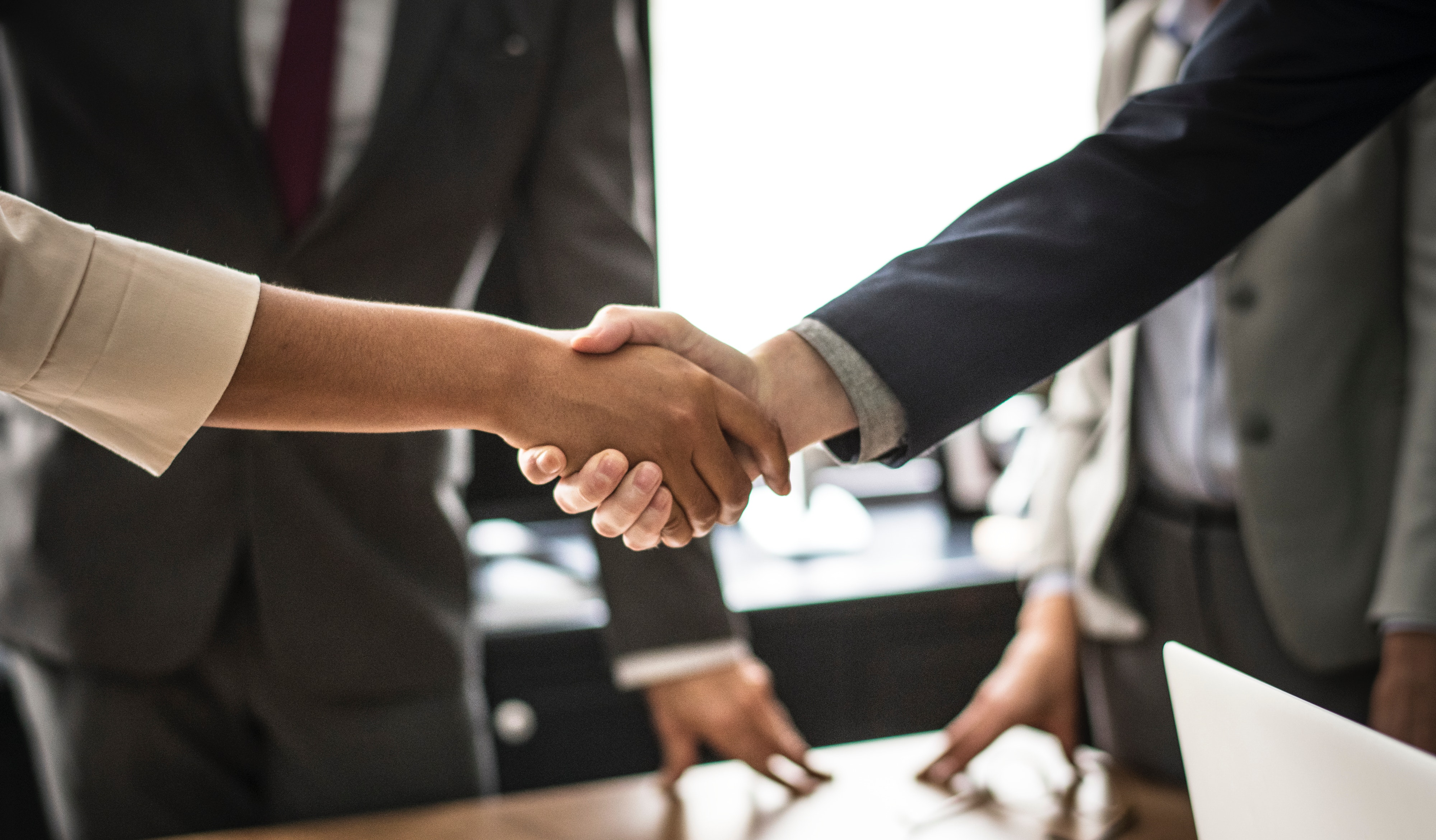 A white person and minority shaking hands at a business office.